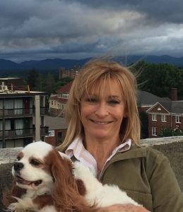 Dr Sondra Harry Smiling Holding Her Dog on a Rooftop